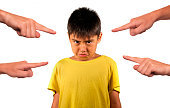 group of hands pointing finger to young sad and stressed schoolboy feeling scared victim of abuse and bullying isolated on white background in kid harassed and bullied at school concept