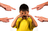 group of hands pointing finger to young sad and stressed schoolboy crying victim of abuse and bullying isolated on white background in kid harassed and bullied at school concept