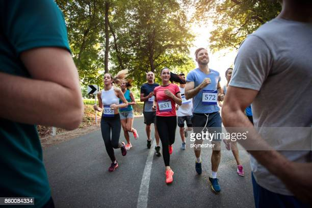 Group of happy athletic people running a marathon race through nature.