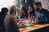 Group of happy business people eating together in restaurant