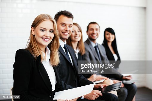 Group of happy business people sitting in a row : Stock Photo