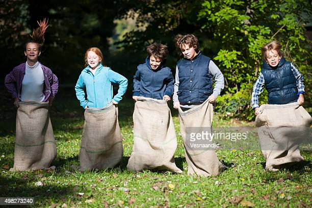 Group of happy children enjoying in a sack race