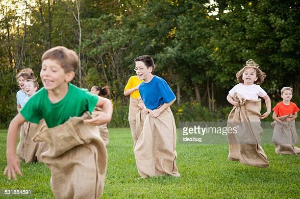 Group of Happy Children Having Potato Sack Race Outside