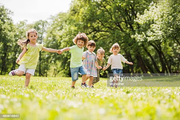 Feliz grupo de crianças a correr no parque.