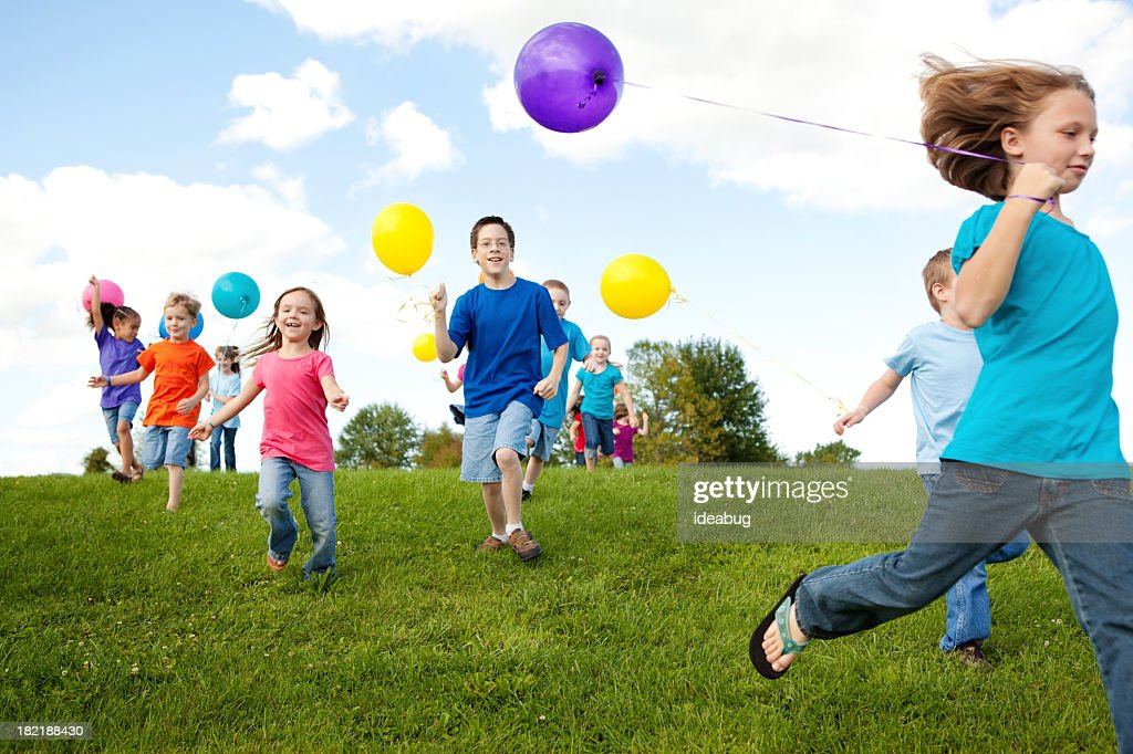 Group of Happy Children Running with Balloons : Stock Photo