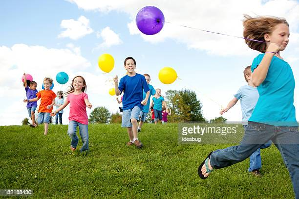 Group of Happy Children Running with Balloons