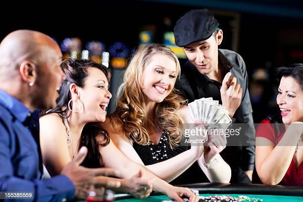 幸せな多様なグループの人々のブラックジャックテーブル