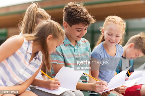 group of happy elementary school students outdoors : Stock Photo