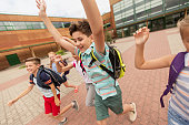 primary education and people concept - group of happy elementary school students with backpacks running and waving hands outdoors (out of focus, motion blurred image)