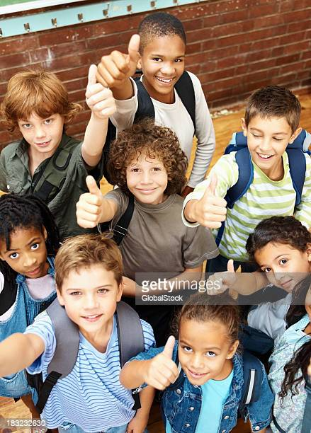 Gruppe von glücklich elementary Studenten, die ein Daumen hoch-Schild