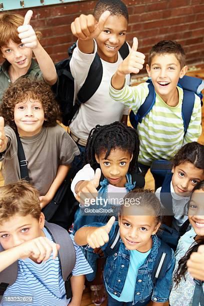 Gruppe von glücklich elementary Studenten zeigen einen Vertrag unterzeichnen