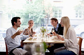 Group of happy friends at restaurant table