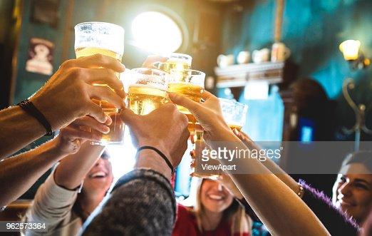Grupo de amigos felices bebiendo y tostado de la cerveza en la cervecería restaurante bar - concepto de amistad con los jóvenes que se divierten juntos en el pub vintage cool - enfoque en vaso de cerveza medio - imagen iso alta : Foto de stock