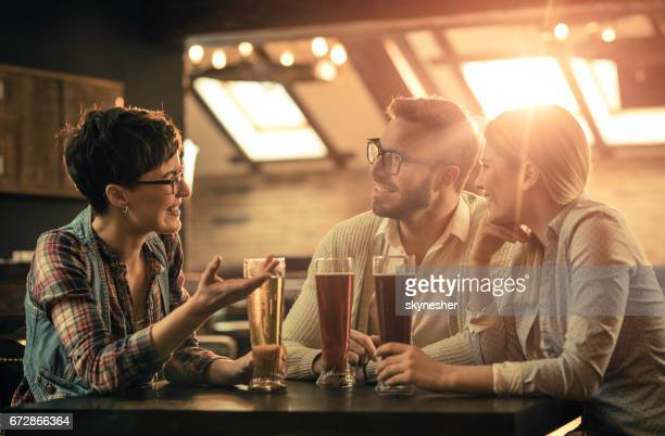 Group of happy friends drinking beer and talking in a bar after work.