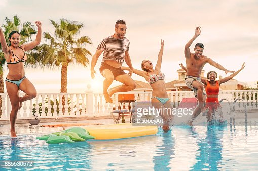 Group of happy friends drinking jumping in pool sunset party outdoor - Young diverse culture people having fun in tropical vacation - Holiday, youth and friendship concept - Main focus on left man : Foto de stock