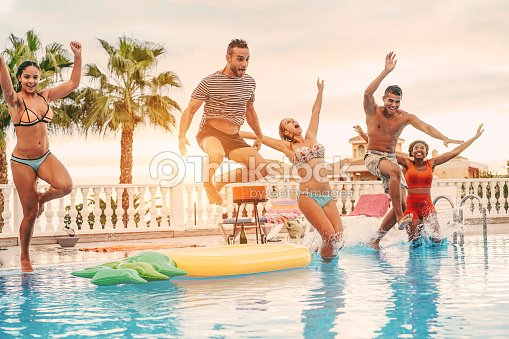 Group of happy friends drinking jumping in pool sunset party outdoor - Young diverse culture people having fun in tropical vacation - Holiday, youth and friendship concept - Main focus on left man : Stock Photo