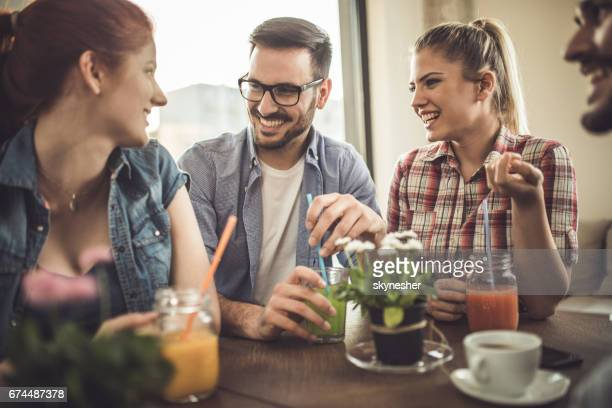 Group of happy friends enjoying in a talk at a cafe.