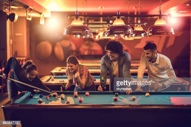 Group of happy friends enjoying in billiard game in a pool hall.