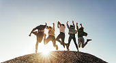 Rear view of group of happy friends having fun on mountain top. Men and women jumping on mountain top against sunset.