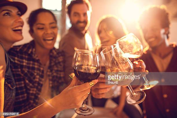 Group of happy friends having fun while toasting with wine.
