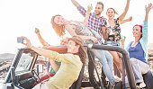 Group of happy friends making party in desert on convertible jeep car - Travel people having fun drinking champagne and taking selfie - Friendship and vacation concept - Focus on man's face with phone