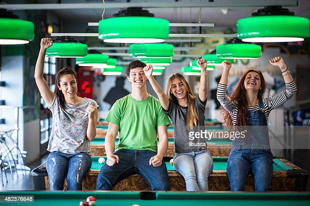 Group of happy friends playing pool
