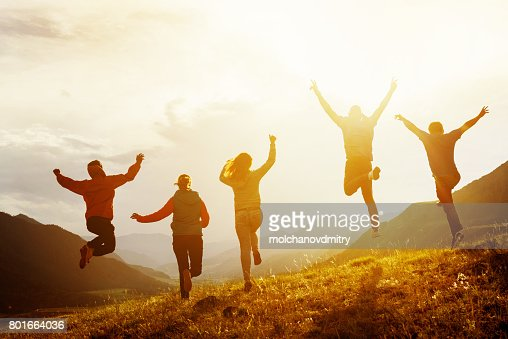 Group of happy friends run and jump : Stock Photo
