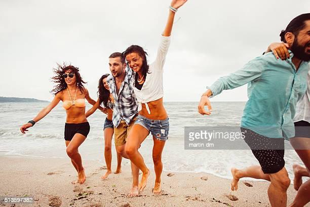 Eine Gruppe von glücklichen Freunde laufen am Strand