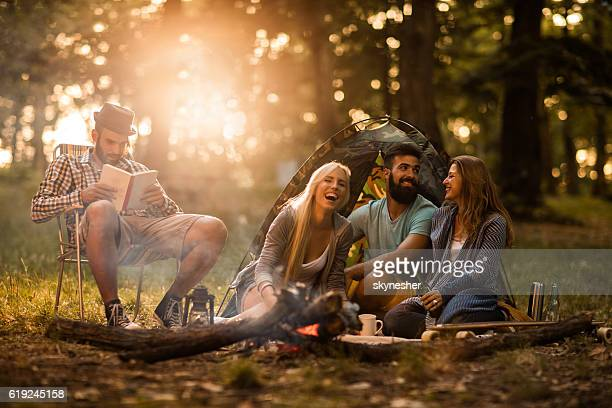Group of happy friends sitting by campfire and having fun.