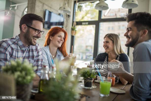 Group of happy friends talking while enjoying in a cafe.