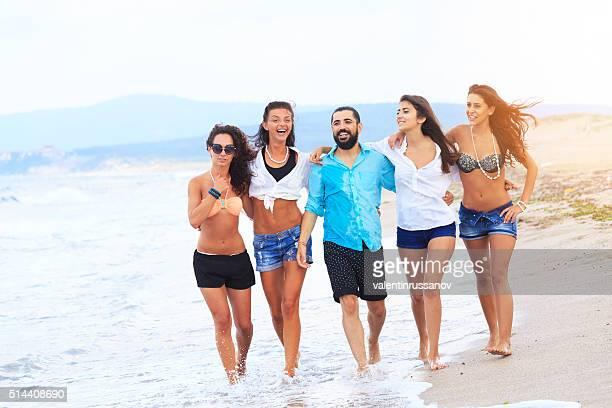 Feliz grupo de amigos andar na praia
