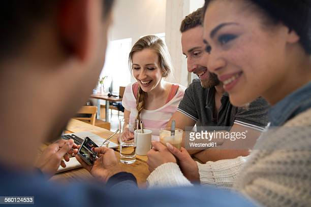 Group of happy friends with laptop and smartphone