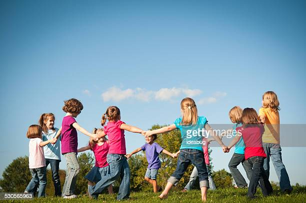 Group of Happy Girls Holding Hands in Circle Outside