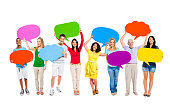 Group Of Happy Multi-Ethnic People Holding Colorful Empty Speech Bubbles