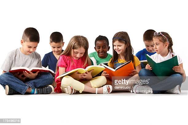 Groupe multiraciale heureux enfants lire des livres à l'école