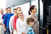 transport, tourism, road trip and people concept - group of happy passengers boarding travel bus