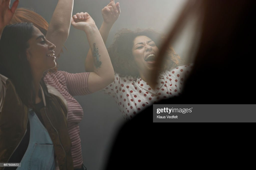 Group of happy people dancing in room with backlight : Stock Photo