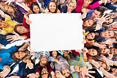 High angle view of large group of happy people holding white paper and looking at the camera. Copy space.