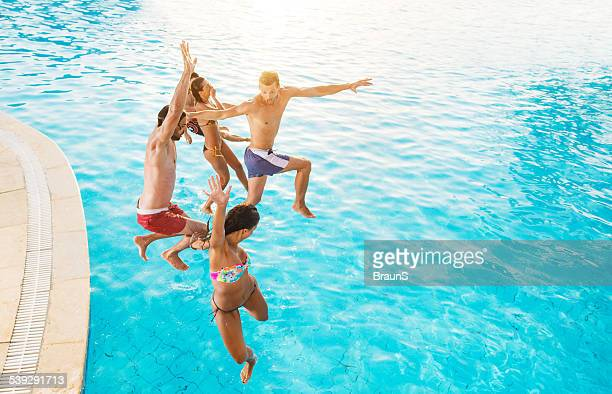 Group of happy people jumping into the swimming pool.