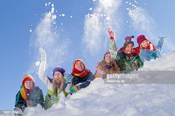 Groupe de happy people allongé sur hill jouant avec de la neige