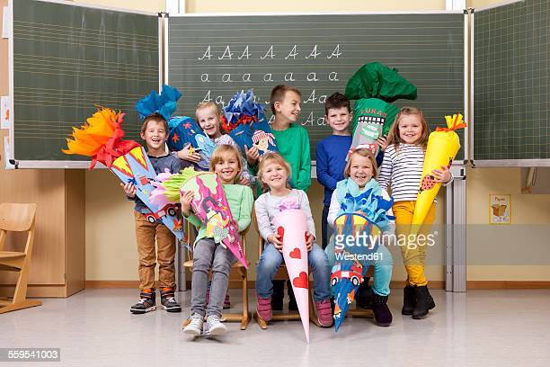 Group of happy pupils with school cones in classroom