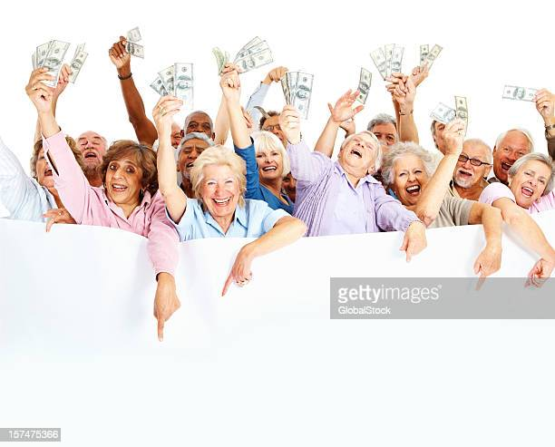 Group of happy senior people holding money