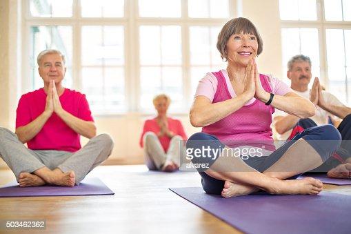 Group of happy seniors practising yoga