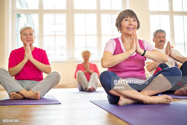 Group of happy seniors practising yoga