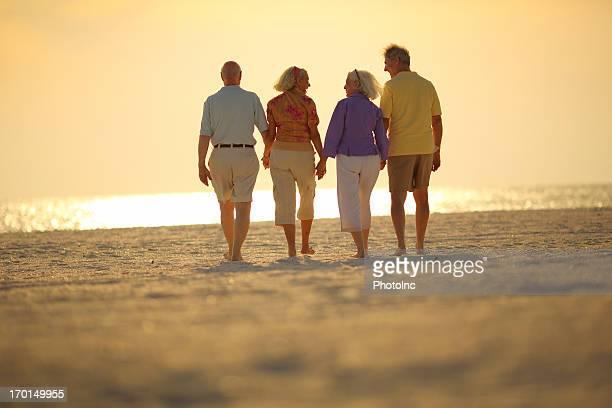 Group of happy Seniors walking on beach at sunset