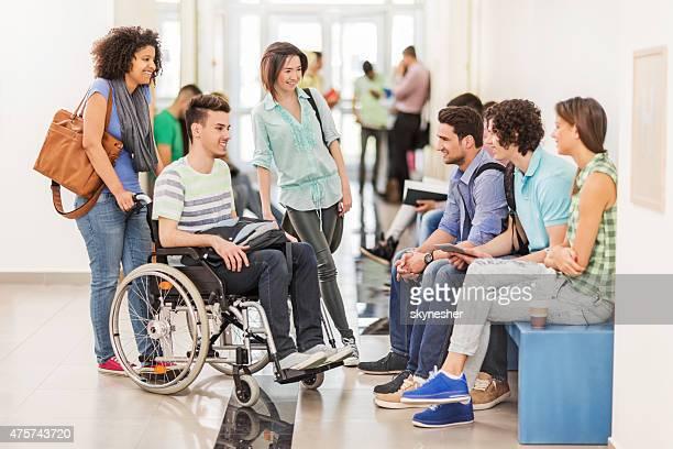 Feliz Grupo de estudiantes la comunicación en el pasillo.