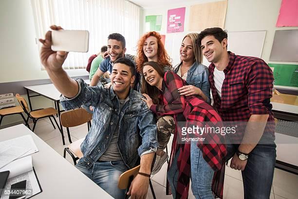 Eine Gruppe von glücklichen Studenten die ein selfie aufnehmen im Klassenzimmer.