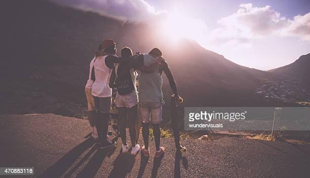 Feliz grupo de amigos adolescentes em pé com longboards