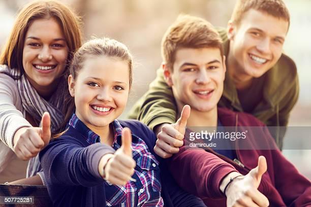 Groupe d'heureux jeunes amis montrant le pouce-up