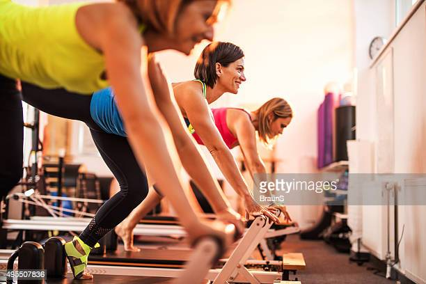 Group of happy women exercising on Pilates training class.